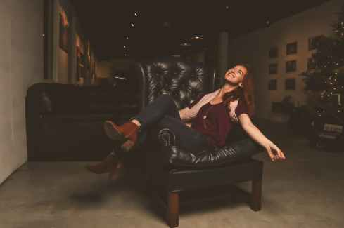 woman in maroon scoop neck shirt sitting on black leather sofa chair