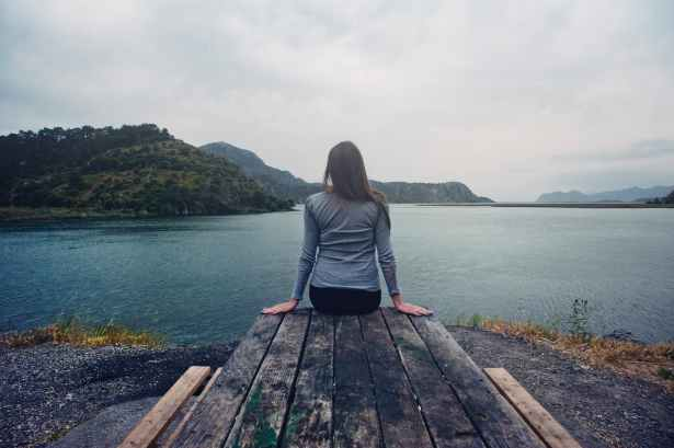 woman wearing gray long sleeved shirt and black black bottoms outfit sitting on gray wooden picnic table facing towards calm body of water at daytime