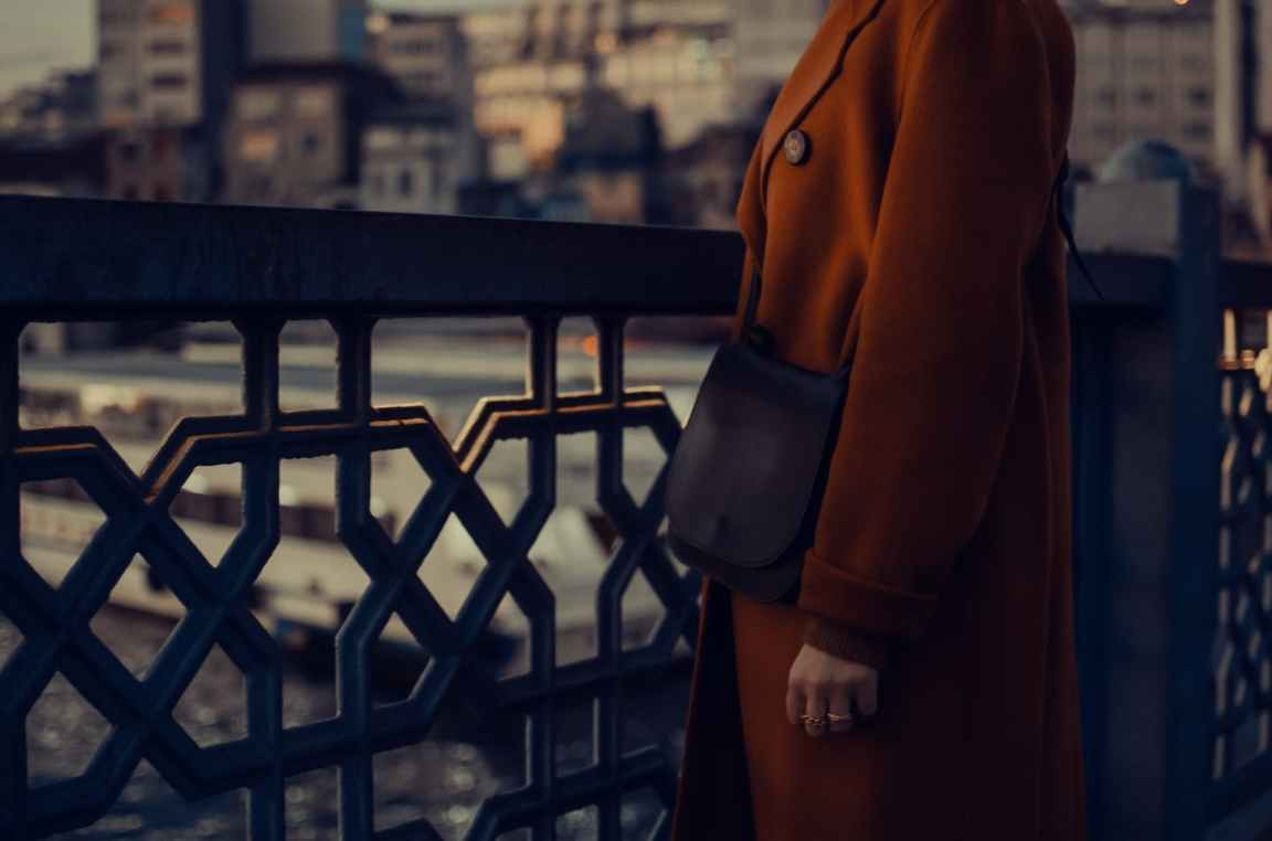 person in brown coat standing beside a metal fence of a bridge